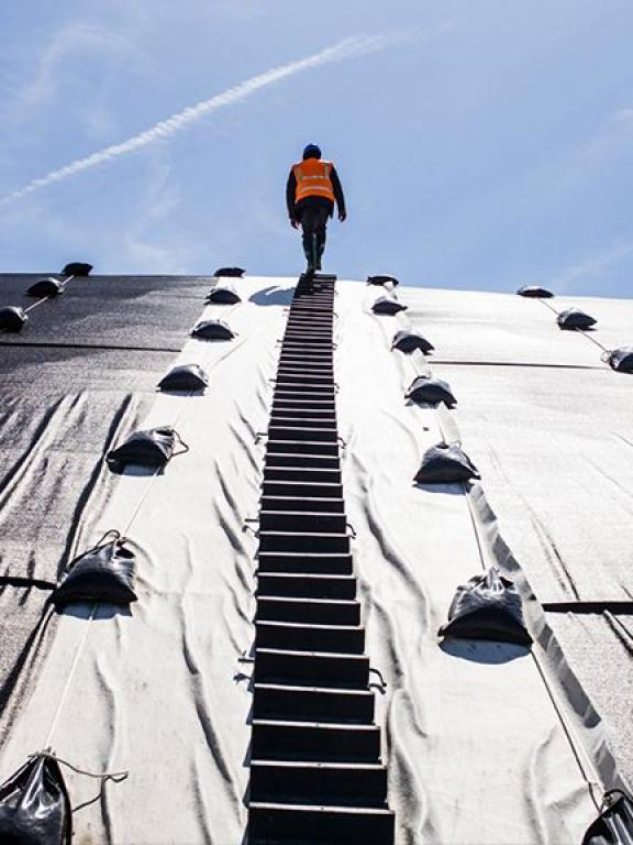 A man walking on a metallic structure